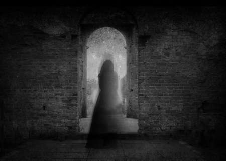 A spooky ghost of a woman in a dress, back to camera, framed by the archway of an old building. With a grunge, vintage, blurred edit. Imagens