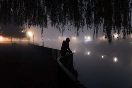 A mysterious hooded figure looking into a river. On a foggy winters night in a city. Reklamní fotografie