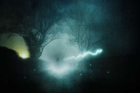 A spooky hooded figure. Surrounded by floating magical lights. Standing on a country road on a foggy winters night. With a grunge, artistic edit
