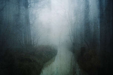 A horror concept of a woodland stream in a dark spooky forest in winter. With a grunge, artistic, edit