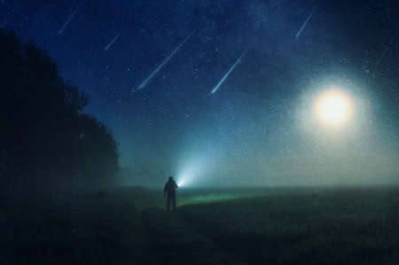 A man standing in the countryside shinning a torch into the darkness. With shooting stars heading towards the earth, against the night sky, With an abstract, artistic, edit