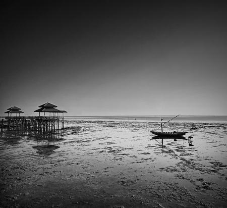 receding: Fisherman activity on receding shore Taken at Kenjeran beach, Surabaya, east Java, Indonesia