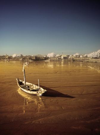 receding: Wrecked boat at receding shore