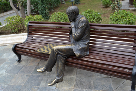 player bench: sculpture chess player on a park bench