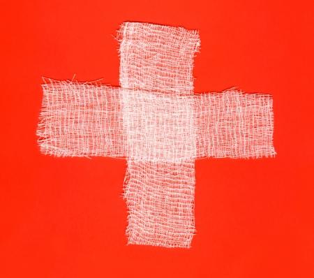 Twee witte bandages vorming van een kruis op rode achtergrond