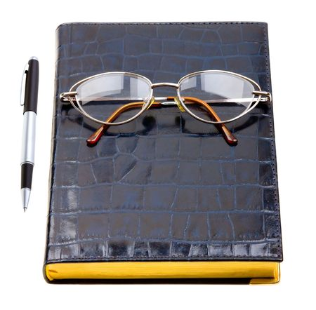 Daily planner with glasses and pen isolated on white background