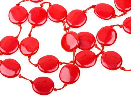 bstract: Close-up beautiful string of red beads isolated on white background