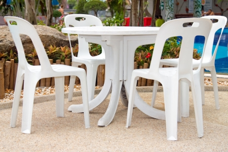 Plastic chairs and a table over a swimming pool