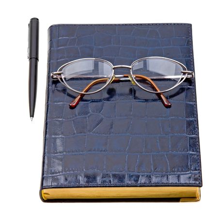 Daily planner with glasses and pen isolated on white background photo
