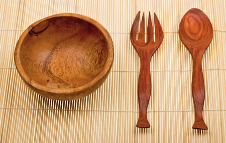 Wooden spoon, fork and basin on bamboo mat photo