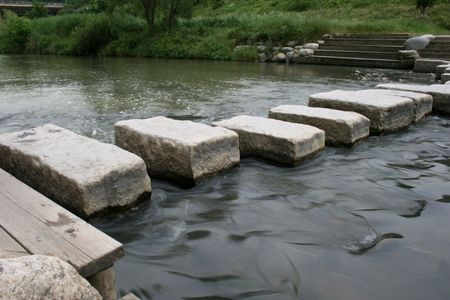 river stones: River crossing with a stepping stone Stock Photo