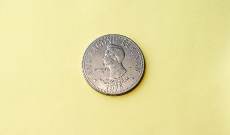 marcos: Old vintage coin circa 1972 depicting the face of Ferdinand Marcos 1972 - in a yellow background
