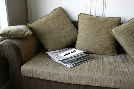 mag: Latest News on a pile of Newspaper on a cozy sofa