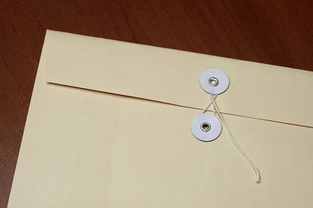 Manila envelope with string with table texture background photo