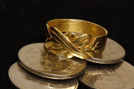 Gold Puzzle ring with coins in a black velvet background. photo