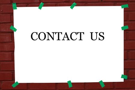 Contact us witten in poster in the street with green tape to a brick wall. photo
