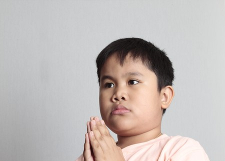 hallowed: Praying young boy in a gray background