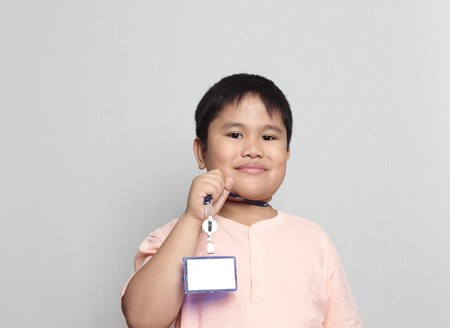 Young boy showing his school identification in a gray background Stock Photo - 7479082