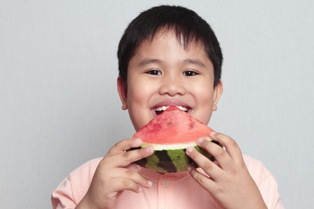 boy eating a slice of watermelon in a gray background photo