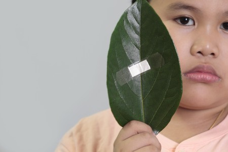 Environment conservation concept - boy holding a leaf with bandage. photo
