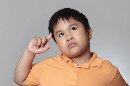 boy thinking and looking up over gray background Stock Photo - 7536214