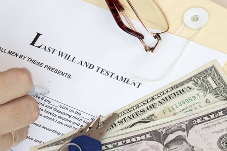 surviving: Last Will and Testament with dollars and hand ready for fill-up the form. Stock Photo