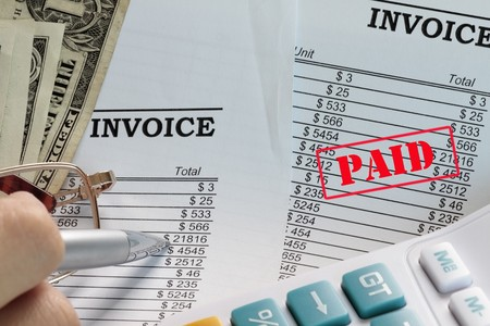 paid: Paid invoice in a spreadsheet with dollars and pen. Stock Photo