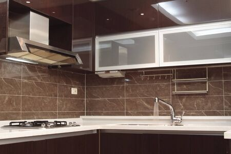 modern kitchen with details, sink, hood, burner, faucet and cabinets. photo