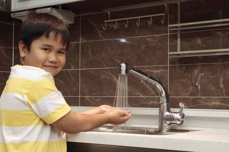 antibacterial soap: Child washing hands in sink in a modern kitchen.