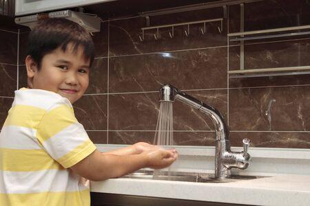 ocd: Child washing hands in sink in a modern kitchen.