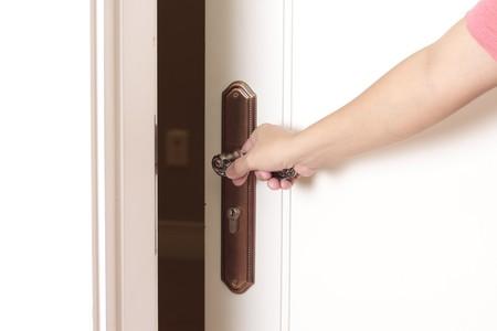 Opening the door with hand on the doorknob  photo