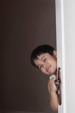 Joyful boy peeping out from behind door concept. photo