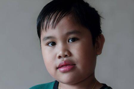 unorthodox: unorthodox closeup portrait of a boy in a gray background