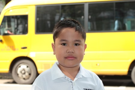 a smiling school boy with a yellow school bus in the background  photo
