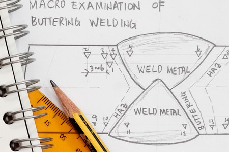 Weld symbol as shown in a drawing paper with spiral notebook and pencil.