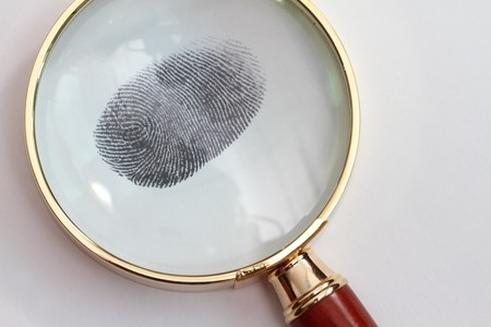 Magnifying glass looking through finger print in a white background photo