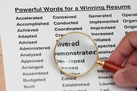 job market: Powerful word for winning a resume- magnifying glass searching for powerful word