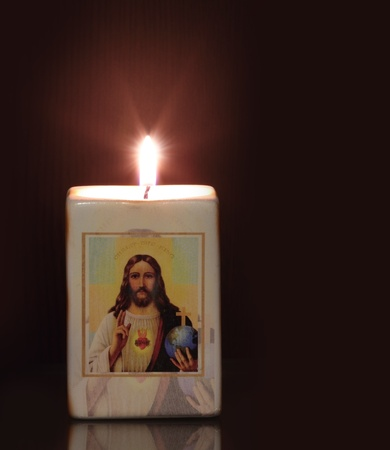 easter candle is burning: candle with religion motiff jesus christ in black background