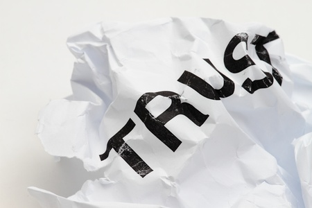 trusted: Trust printed on paper crumpled on white background abstract