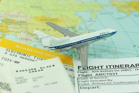 Travel abstract trip with boarding pass, flight itinerary and toy airplane. Shallow depth of field.