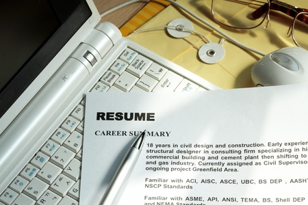Resume in a computer keyboard with manila envelop and eyeglass
