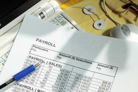 Payroll spreadsheet with computer monitor and mouse Stock Photo