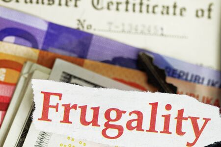 frugality: Frugality abstract - cutout money and certificate of title. Stock Photo