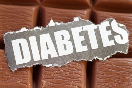 Diabetes cut out in a bar of chocolate background.