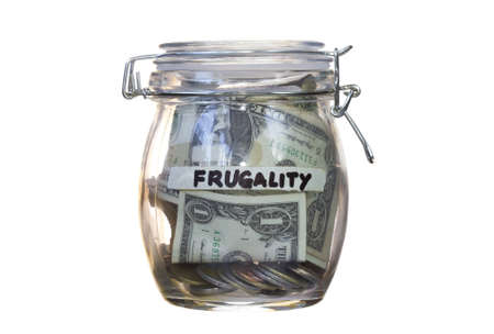 frugal: Frugality concept- jar close full of coins and dollar. Isolated in white background. Stock Photo