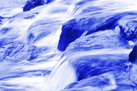 saturated color: Small brooks in blue saturated color mixed with white water splash Stock Photo