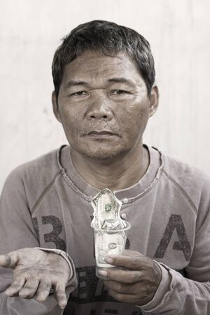 A homeless man holding a cup with money photo