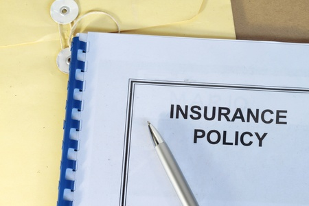 policies: insurance policy folder on desk in office with pen and manila envelop