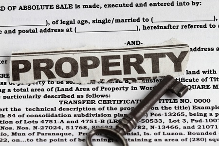 house exchange: Property abstract for deed of sale with a vintage key in the foreground