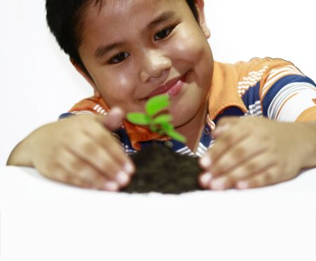 boy looking a  green plant in a white background photo